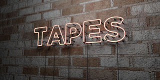 TAPES - Glowing Neon Sign on stonework wall - 3D rendered royalty free stock illustration Royalty Free Stock Photo