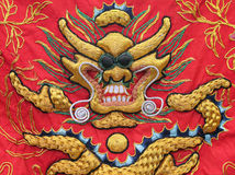 Tapestry of a Golden Dragon on a Red Silk Background Royalty Free Stock Image