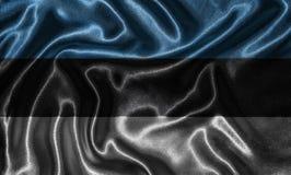 Tapet av den Estland flaggan och den vinkande flaggan vid tyg Royaltyfri Bild
