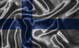 Tapet av den Finland flaggan och den vinkande flaggan vid tyg Royaltyfri Fotografi