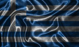 Tapet av den Grekland flaggan och den vinkande flaggan vid tyg Royaltyfria Foton