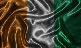 Tapet av Elfenbenskustenflaggan och den vinkande flaggan vid tyg Arkivfoto