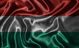 Tapet av Ungernflaggan och den vinkande flaggan vid tyg Royaltyfri Foto