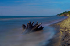 Tapet - stranden med en stubbe i lång exponering royaltyfria bilder