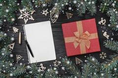 Tapeta zima wakacje na czarnym tle Czerwony prezent i drewniane zabawki Jedlinowi drzewa wokoło List dla Święty Mikołaj z przestr obrazy stock