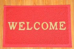 Tapete bem-vindo do vermelho no fundo de madeira Fotos de Stock Royalty Free