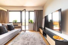 Tapete cinzento, cortinas e um sofá à moda em um apartamento de estúdio acolhedor fotos de stock