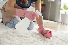 Tapete da limpeza da jovem mulher na sala fotografia de stock