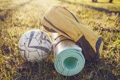 Tapete da trouxa do piquenique e bola de futebol na grama no sol brilhante do verão Fotografia de Stock Royalty Free