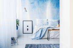 Tapete e cartaz modelados no interior azul do quarto com cama outra vez Imagem de Stock Royalty Free
