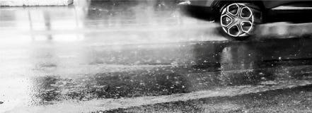 Tapete eines Autos, das schnell auf der nassen Straße im Regen, in Schwarzweiss läuft stockfotografie