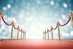 Tapete vermelho com barreira da corda no fundo azul Fotografia de Stock Royalty Free