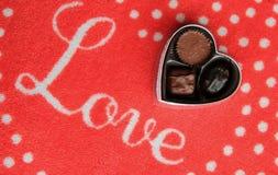 Tapete vermelho com o amor da palavra baseado num guião através da parte superior e do trio dos chocolates Fotografia de Stock Royalty Free