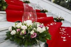 Tapete vermelho do casamento com velas brancas em escadas da igreja fotografia de stock