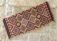 Tapetes turcos brilhantes que penduram em uma parede de pedra fotografia de stock