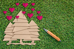 Tapetuje cięcie drzewo i różowi serce na zielonej trawie Fotografia Stock