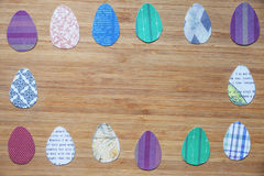 Tapezieren Sie farbige Ostereier werden vereinbart in einem rechteckigen Rahmen auf einem hölzernen Brett Lizenzfreie Stockfotos
