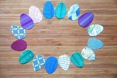 Tapezieren Sie farbige Ostereier werden vereinbart mit einem ovalen Rahmen, auf einem hölzernen Brett Stockfotos