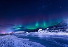 Tapezieren Sie Norwegen-Landschaftsbeschaffenheit der Berge der Gebäude-Schneestadt Spitzbergens Longyearbyen Svalbard auf einem  Stockbild