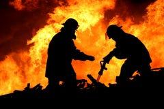 Tapfere Feuerwehrmänner im Schattenbild Stockbild