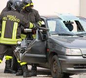 Tapfere Feuerwehrmänner mit pneumatischen Scheren schnitten die Blätter des Autos lizenzfreie stockbilder
