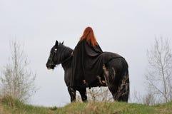 Tapfere Frau mit dem roten Haar im schwarzen Mantel auf friesischem Pferd Stockfoto