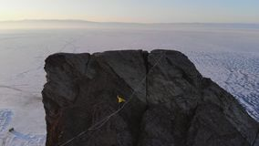 Tapfere junge Frau, die auf einen Riemen auf einem hohen Felsen geht stock video