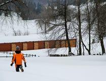 Tapferer Junge, der durch den weißen Schnee geht Stockfotos