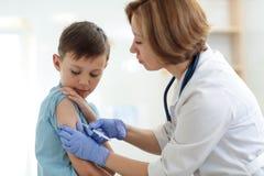 Tapferer Junge, der Einspritzung oder Impfstoff mit einem Lächeln empfängt stockfoto