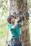Tapferer Junge des Active, der an Auslandsklettern am Erlebnispark genießt Lizenzfreies Stockfoto
