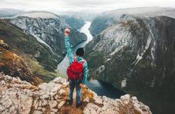 Tapferer Mann, der in Norwegen-Berge stehen auf Klippe reist stockbilder