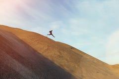 Tapferer Mann mit dem Rucksack, der auf eine Düne läuft und springt Stockbild