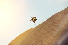 Tapferer Mann mit dem Rucksack, der auf eine Düne läuft und springt Lizenzfreies Stockfoto