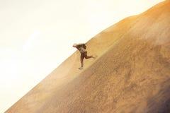 Tapferer Mann mit dem Rucksack, der auf einer Düne läuft Lizenzfreies Stockbild