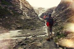 Tapferer Mann mit einem Rucksack, Fotografien Gletscher und Berglandschaft auf einem Smartphone Stockbilder