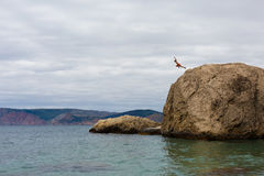 Tapferer Mann springt von hohem Cliff Rock Into Water von Meer Lizenzfreie Stockfotografie