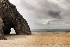 Tapferer Ozean, Felsformationen und bewölkter Dramahimmel auf dem Strand Lizenzfreie Stockbilder