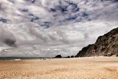 Tapferer Ozean, Felsformationen und bewölkter Dramahimmel auf dem Strand Stockfotografie