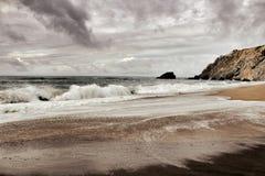 Tapferer Ozean, Felsformationen und bewölkter Dramahimmel auf dem Strand Lizenzfreies Stockbild