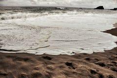 Tapferer Ozean, Felsformationen und bewölkter Dramahimmel auf dem Strand Stockfotos