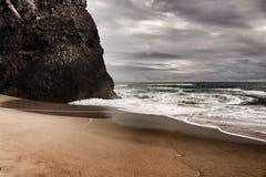 Tapferer Ozean, Felsformationen und bewölkter Dramahimmel auf dem Strand Stockbilder