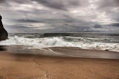 Tapferer Ozean, Felsformationen und bewölkter Dramahimmel auf dem Strand Stockfoto