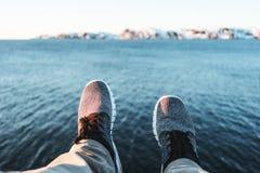 Tapferer Reisender, der auf Klippe und Blicken auf Beinen und Schuhen sitzt Pov-Ansicht über Füße auf Hintergrund von Ozean und v Stockbilder