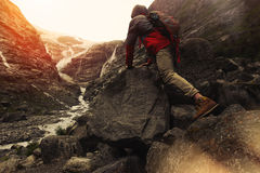 Tapferer Reisender mit einem Rucksack, der auf einem Felsen, gegen den Hintergrund eines Gletschers klettert Lizenzfreies Stockfoto
