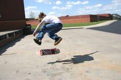 Tapferer Skateboardfahrer, der leichten Schlag 360 tut Stockfotografie