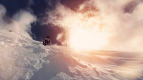 Tapferer Snowboarder mit einem Rucksack klettert oben den Berg Lizenzfreie Stockbilder