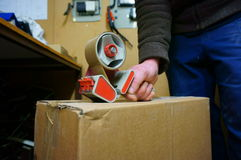 Taping box A. Photograph of a man taping a cardboard box in a factory Stock Image