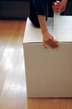 Taping a box up. Person taping a white box up to seal royalty free stock image