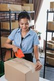 Taping carton boxes to be shipped. Young woman packing and taping carton boxes to be shipped in her office royalty free stock photo