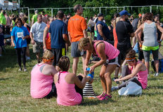 Taping up shoes. Athletes tape shoes onto their feet so they don't come off in the thick wet mud, at  the  July 2014 mudathlon, in northwest Indiana Stock Images